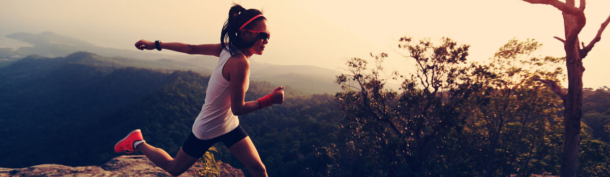 athletic woman running on trail at high elevation Colorado Allergy & Asthma Centers