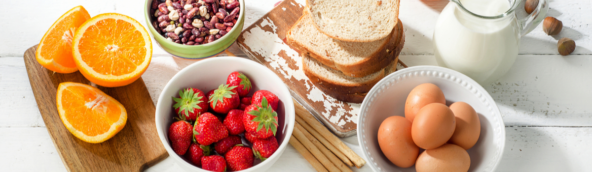 healthy breakfast food with eggs strawberries oranges bread and mile Colorado Allergy & Asthma Centers