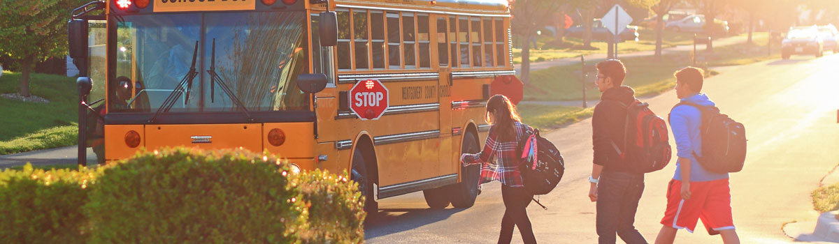 three high school students walking across the street to get on the school bus Colorado Allergy & Asthma Centers